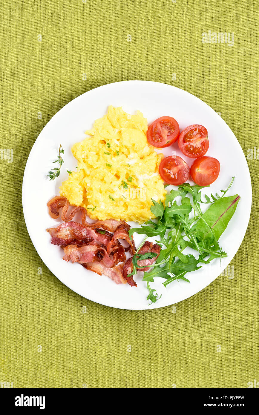 Plate with scrambled eggs, bacon and vegetable salad, top view - Stock Image