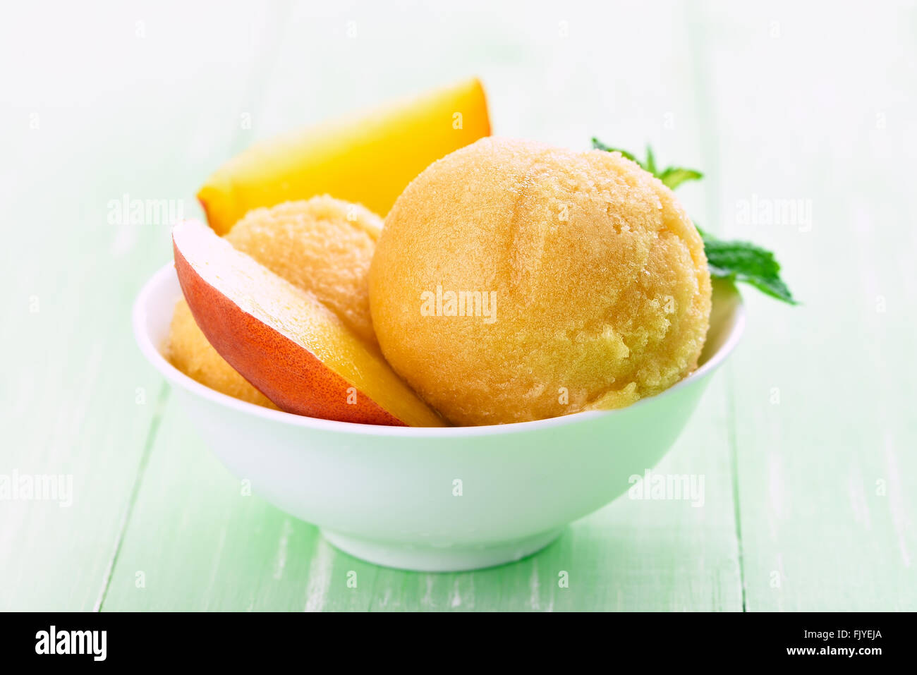Apricot peach ice cream and slices, close up view - Stock Image