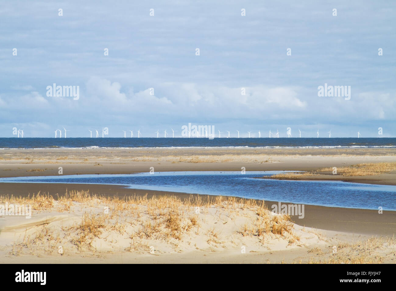 Offshore windpark in the north sea view from the beach of the Dutch island Schiermonnikoog - Stock Image