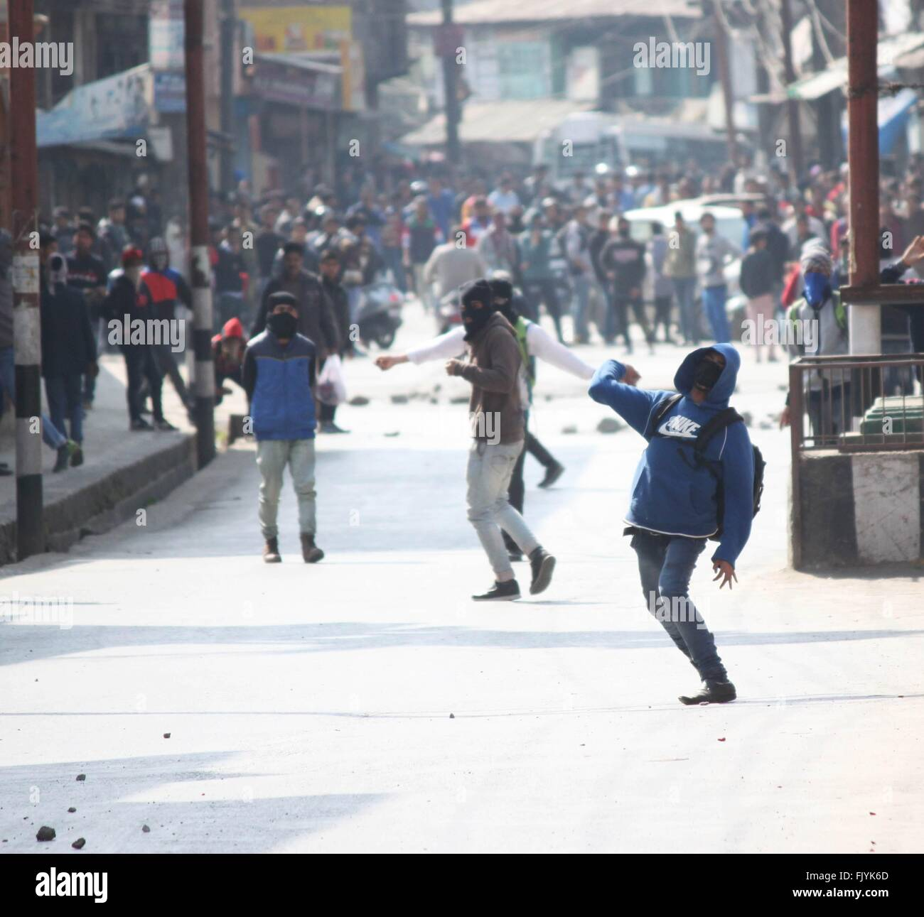 Kashmiri protester throws stone towards police during clashes in Srinagar. - Stock Image