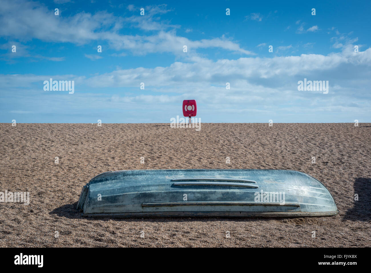 An upturned boat and lifebelt at the beach in West Bay, Dorset, England - Stock Image