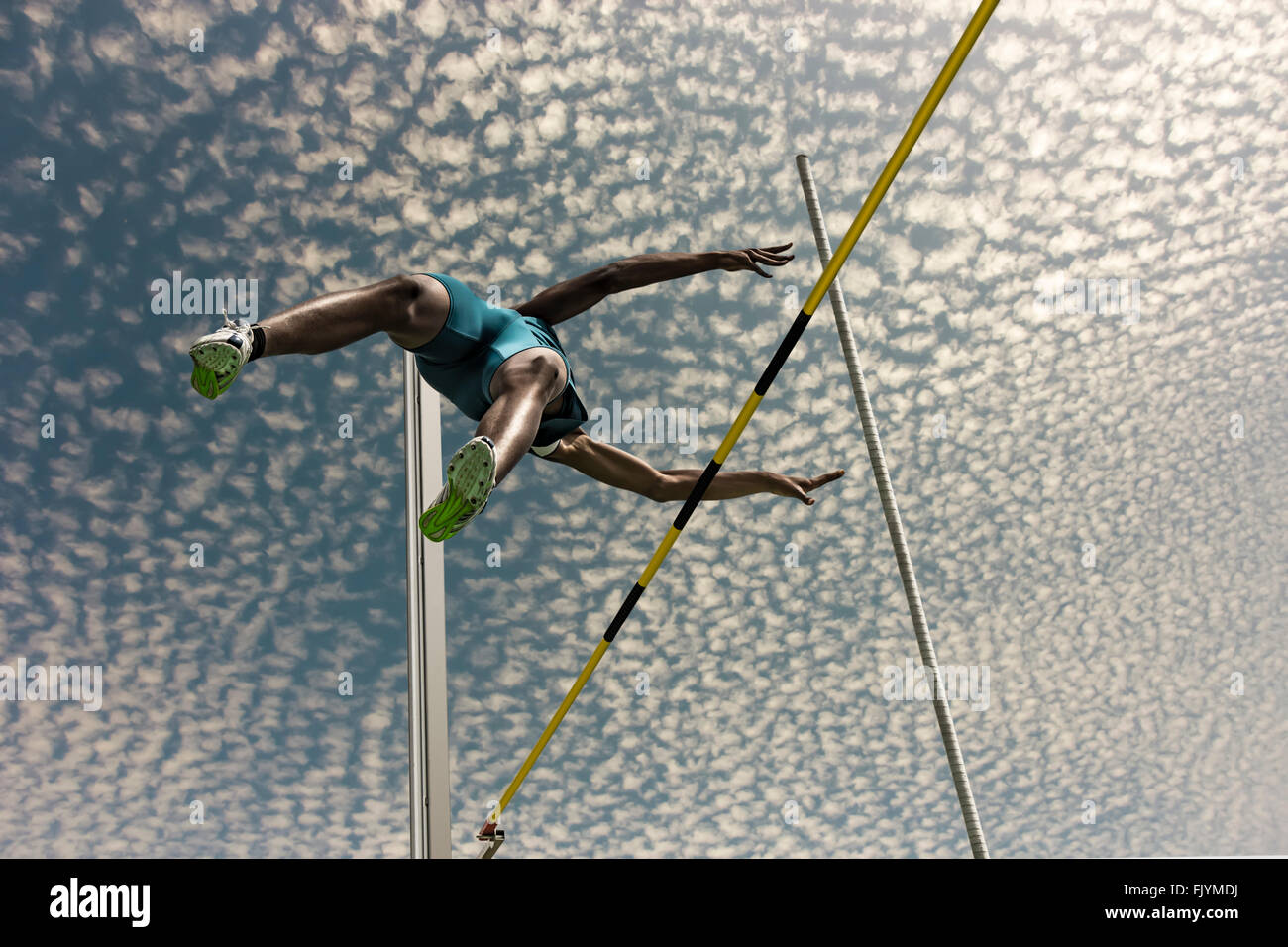 Male pole vaulter jumps  over the yellow black striped bar - Stock Image