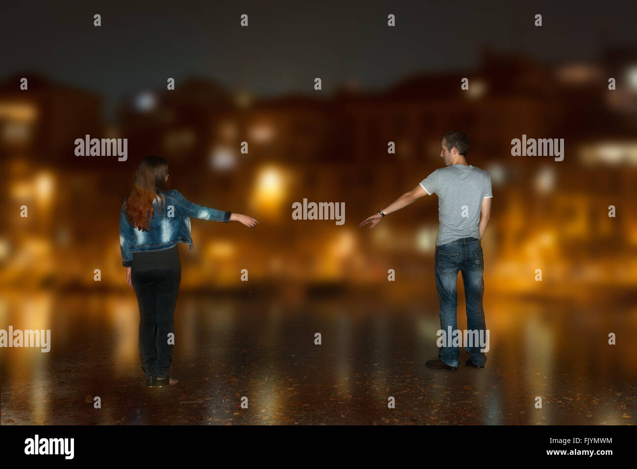 Couple from back side sent arms to each other in night town - Stock Image