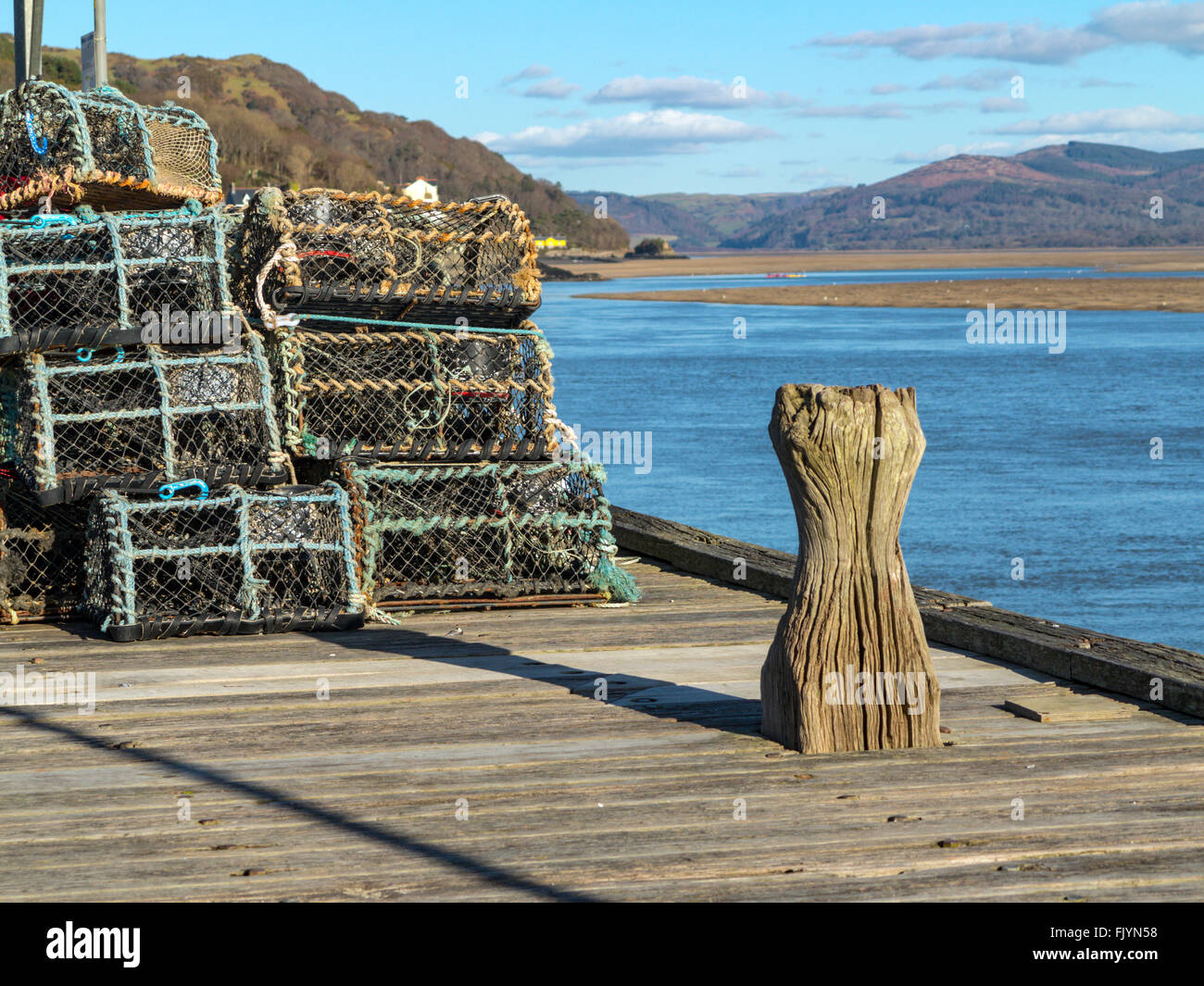Old wooden bollard on a jetty near lobster pots and the distant wooded mountainsides of the Dyfi estuary. - Stock Image