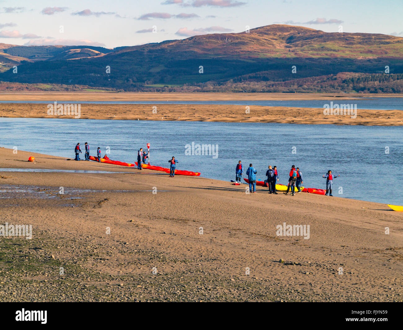 young canoeists gather by the waters edge to ready the canoes for lifting out of the river Dyfi estuary. Stock Photo