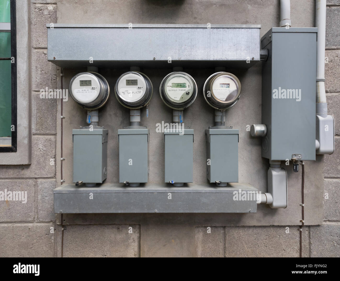 Line up of four electric power meters on side of apartment complex Stock Photo