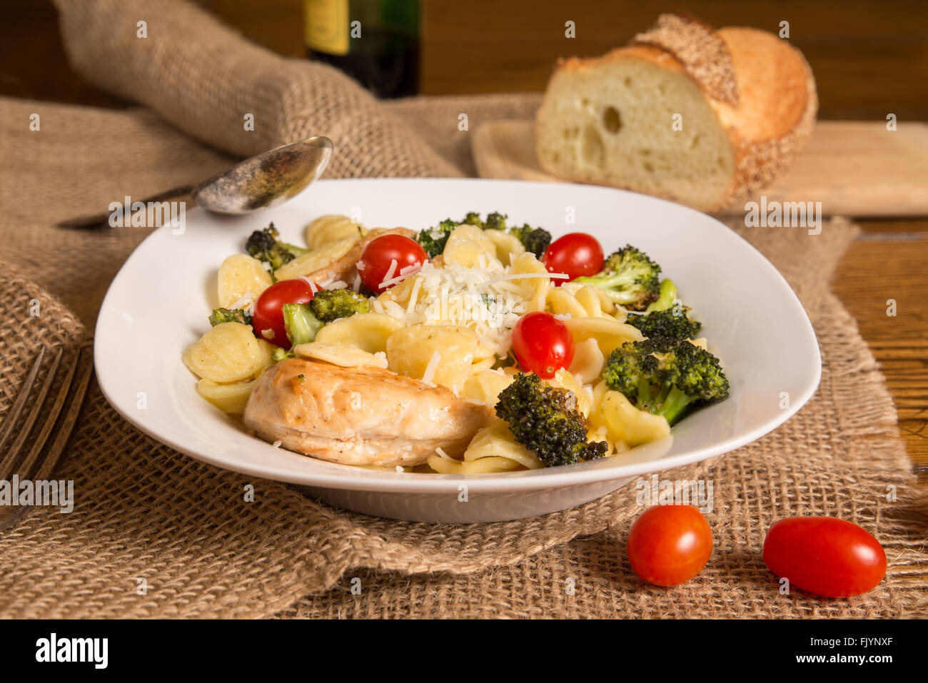 Authentic Italian meal with homemade orecchiette pasta, chicken, broccoli, tomatoes. Loaf of Italian bread and bottle - Stock Image