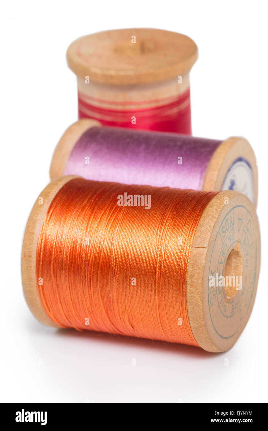 Three colorful spools of orange, purple and red nylon thread on white background - Stock Image