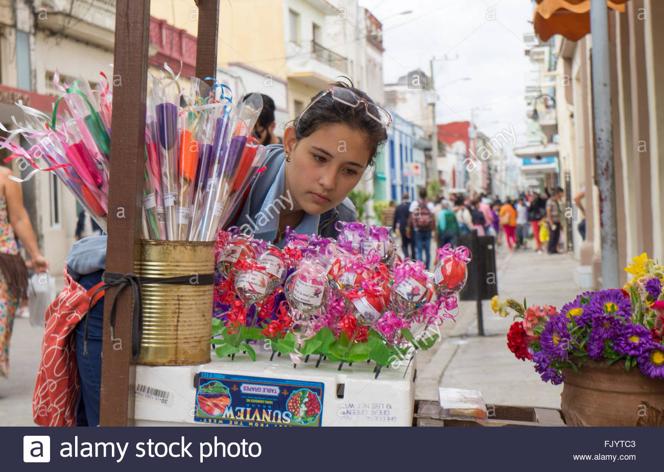 Highschool student picking flowers from a private stand in the boulevard area. - Stock Image
