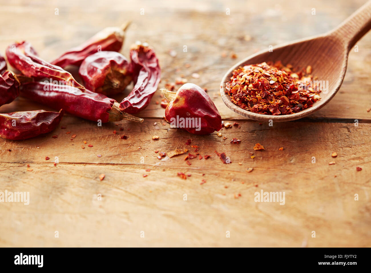 Wooden spoon with red chili pepper flakes and whole red peppers - Stock Image