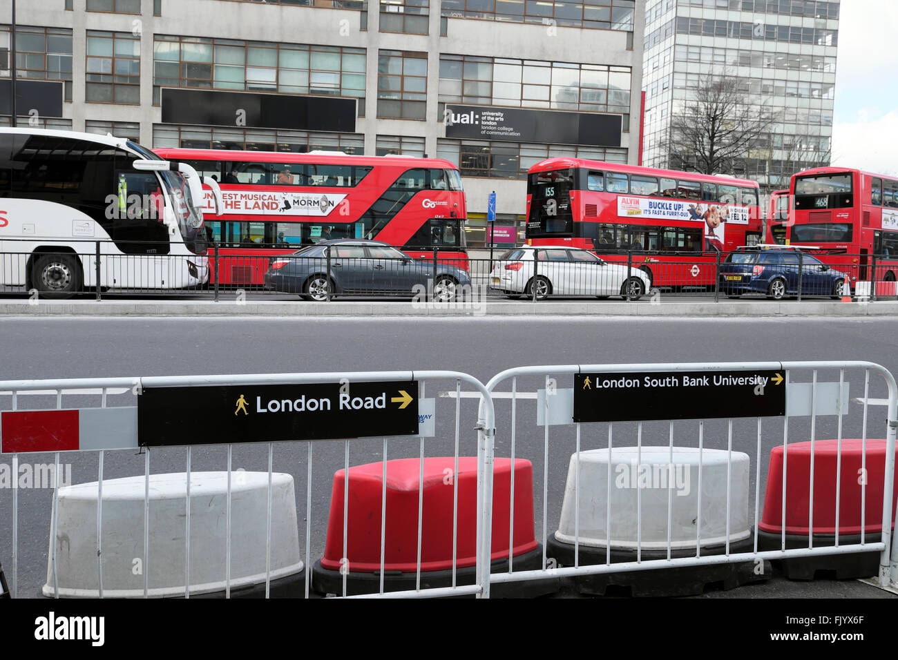 Buses & cars in traffic and roadworks bollards pedestrian fence road outside UAL at the Elephant & Castle - Stock Image