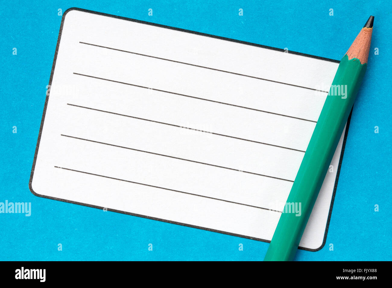School exercise book with empty name label and pencil - Stock Image