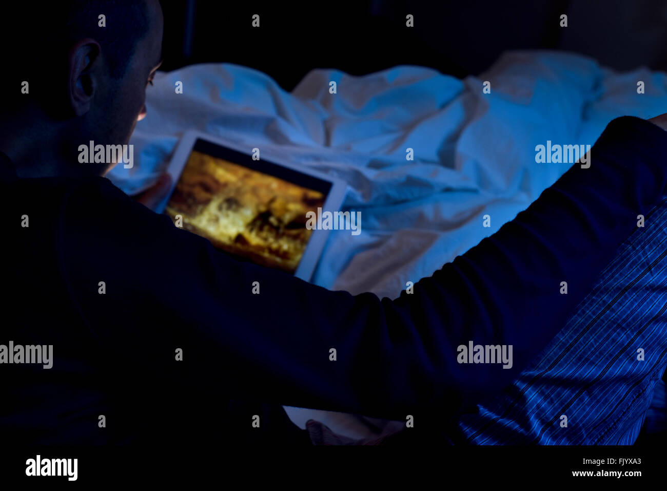 a young caucasian man lying on the bed watches a movie or a series in streaming in his tablet computer, at night - Stock Image