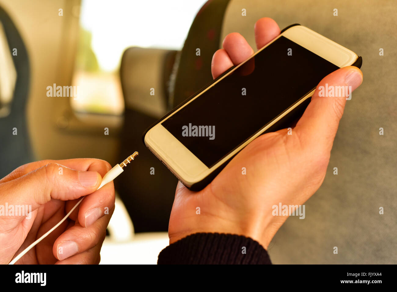 closeup of a young caucasian man plugging the earphones in his smartphone in a train or a subway - Stock Image