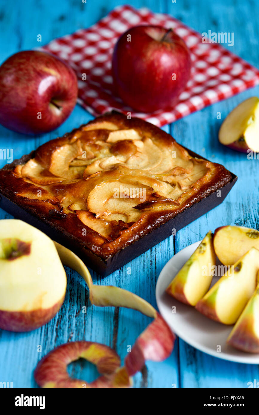 closeup of an apple cake and some red apples on a blue rustic wooden table - Stock Image