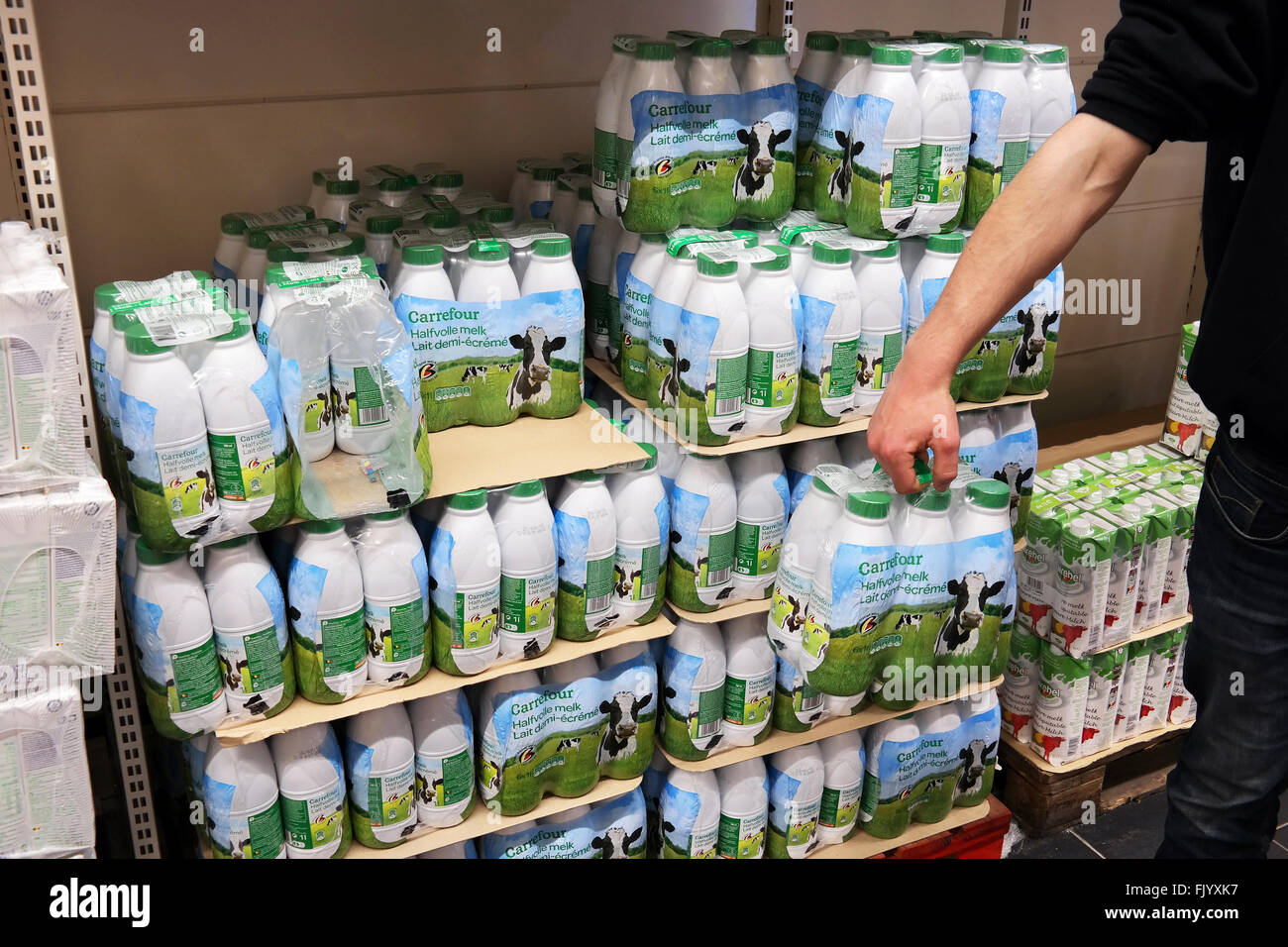 Milk in plastic bottles printed with cows. - Stock Image