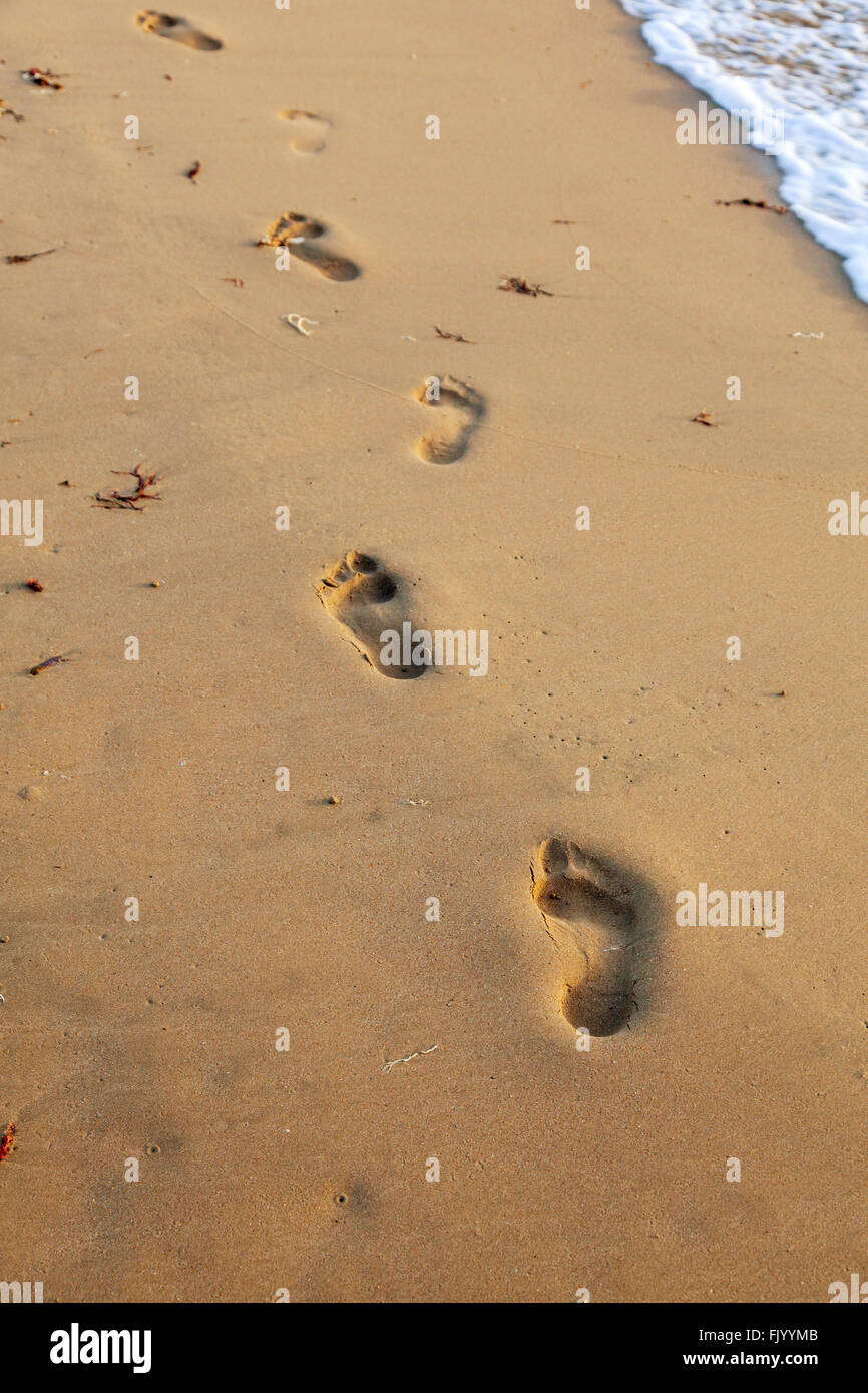 Bare foot prints in the sand. - Stock Image