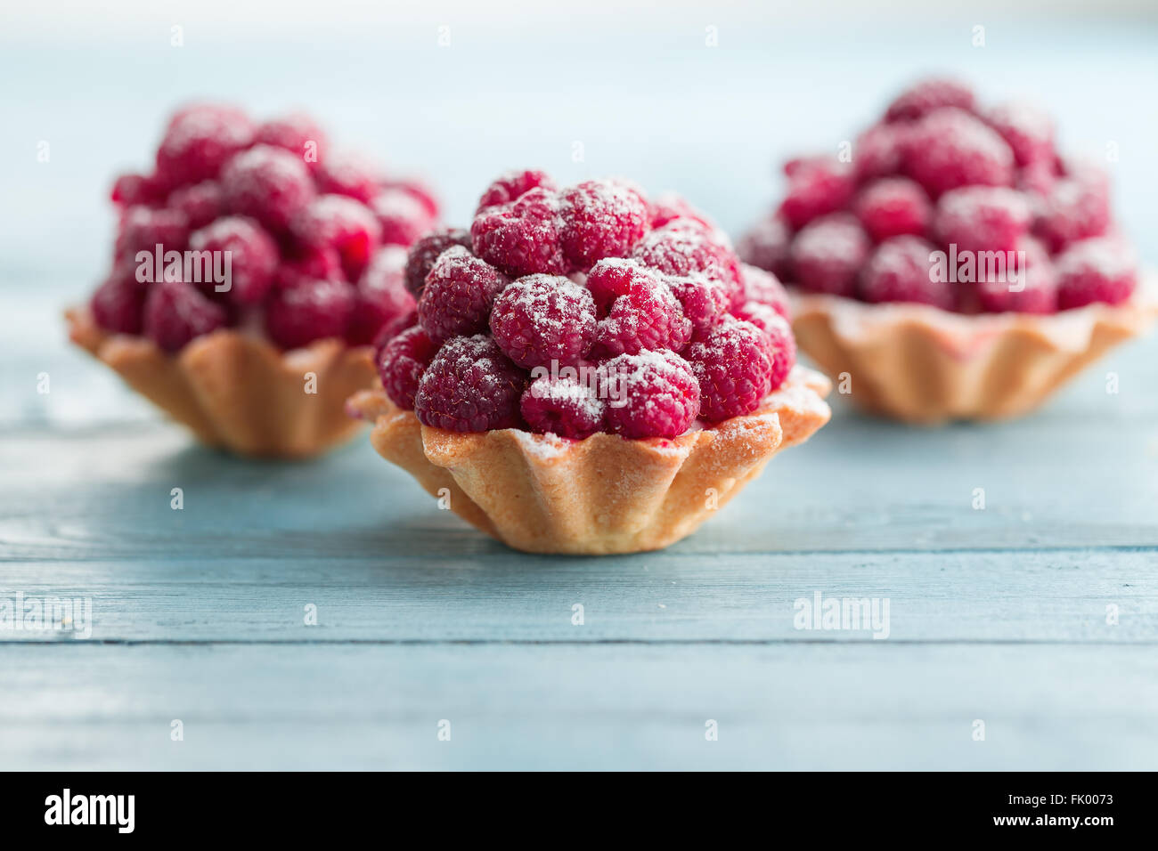 Raspberry tartlets with cream filling and dusted with icing sugar - Stock Image