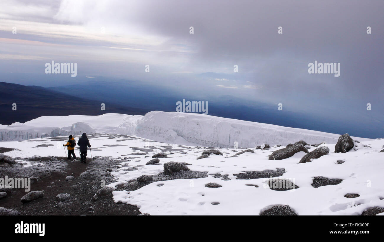 Two brothers walking along the trail from Stella Point to Uhuru Peak at the summit of Mount Kilimanjaro. - Stock Image
