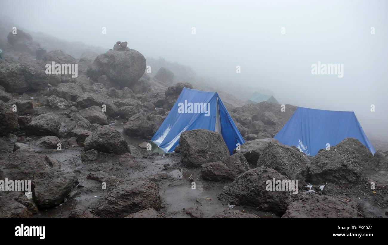 Two blue tents set up amongst large lava rocks at Barafu Hut campsite on the slope of Mount Kilimanjaro. - Stock Image