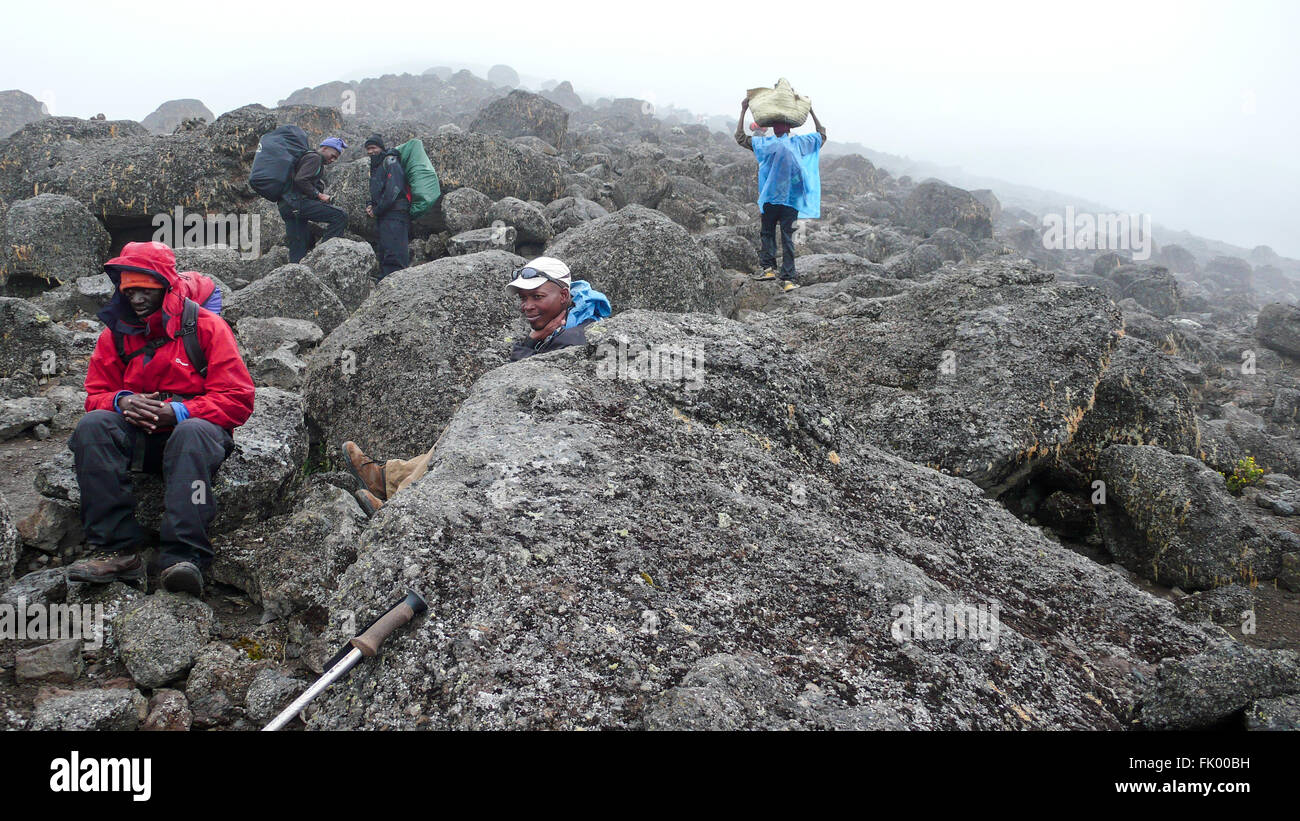 African mountain climbing guides sitting amongst lava boulders. - Stock Image