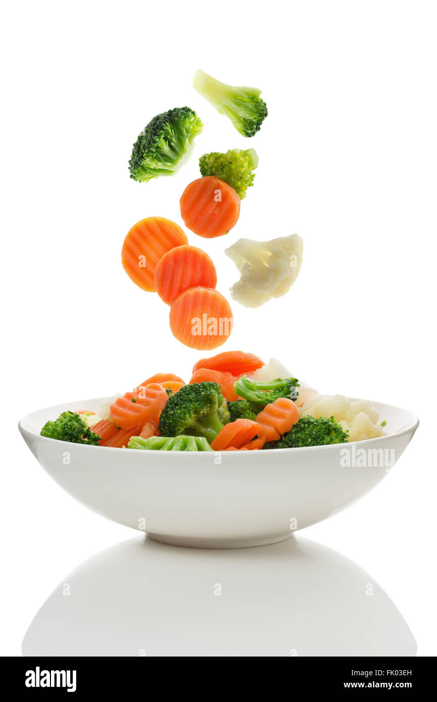Mixed vegetables falling into a bowl of salad - Stock Image