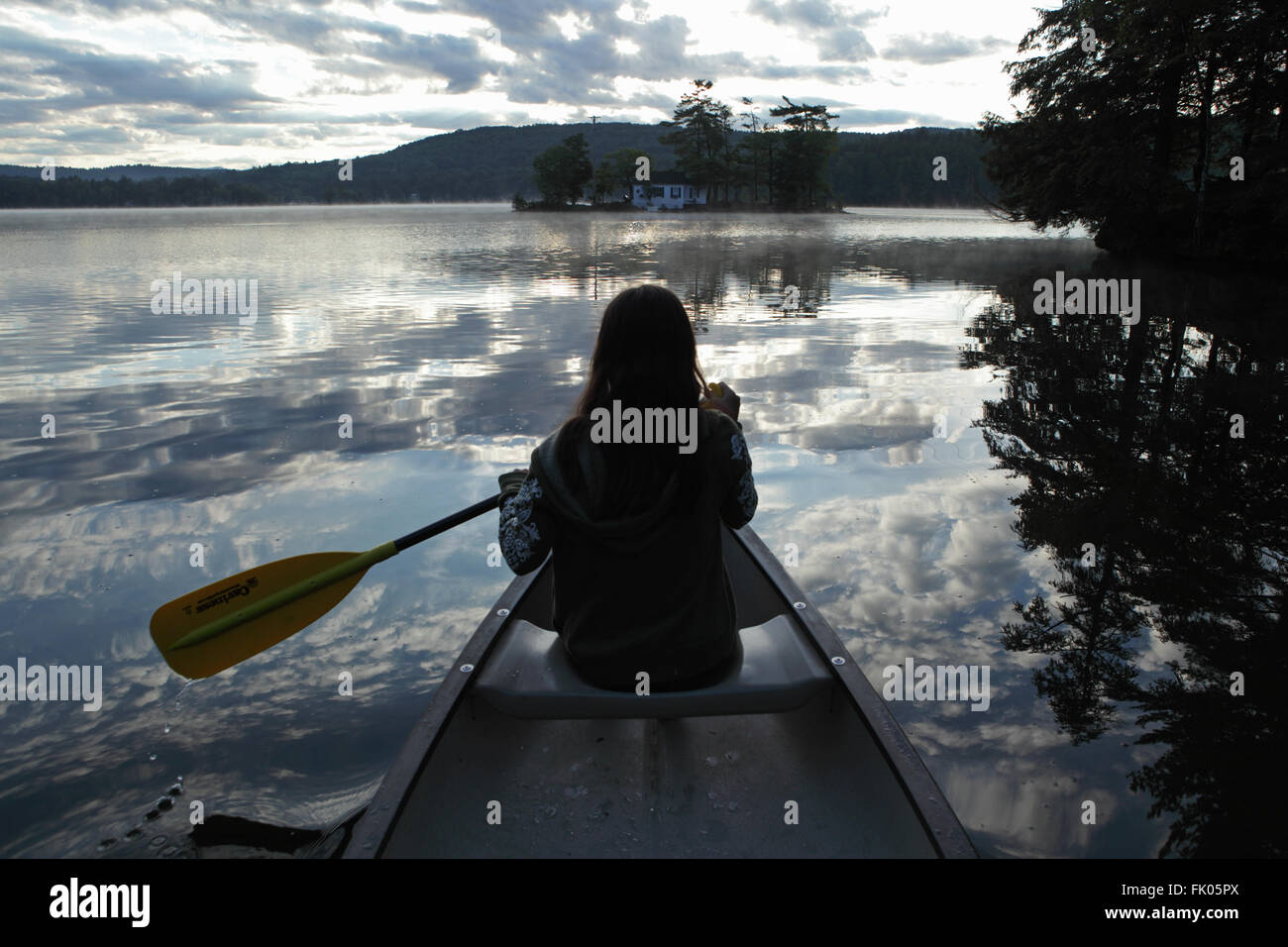 Young girl paddling a canoe on a lake reflecting clouds as the sun rises over a hill. - Stock Image