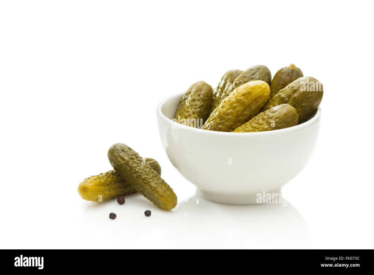 Pickled green gherkins on white background - Stock Image