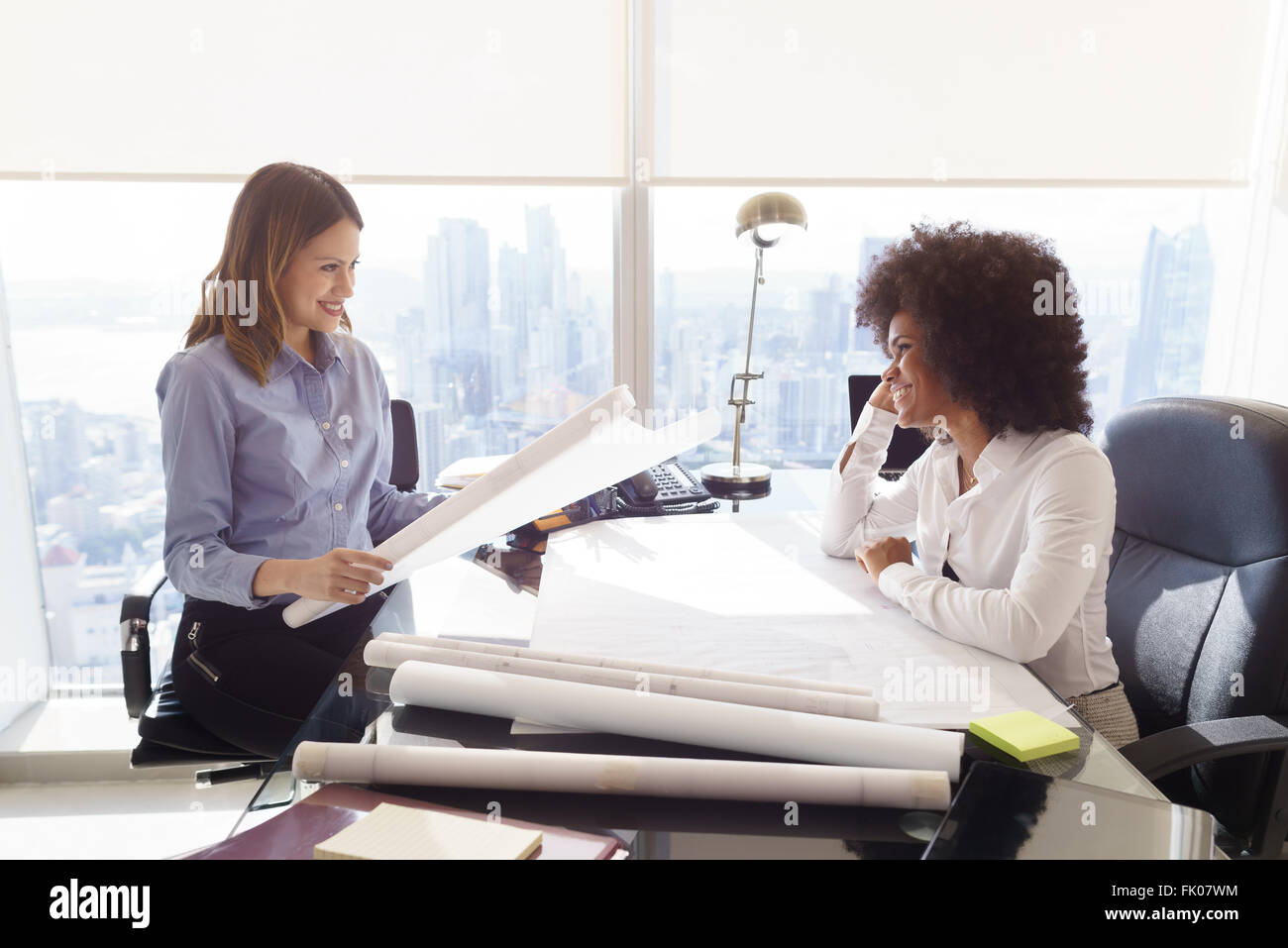 Team of two female architects, sitting at desk in office. The women talk and smile reviewing a building plan. Medium - Stock Image