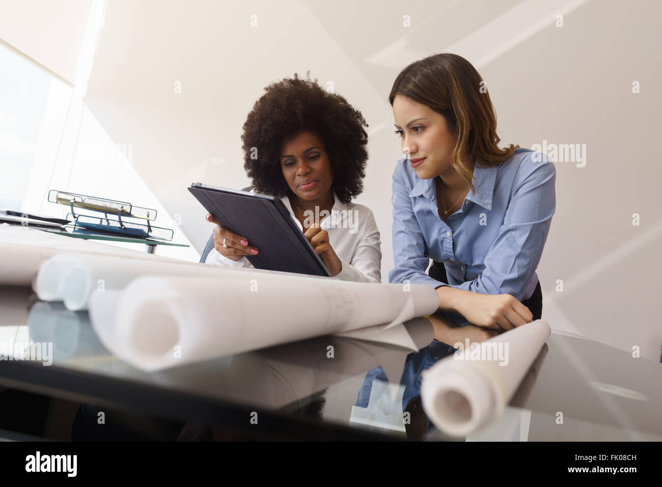 Two architects in modern office building, sitting on desk with blueprints and housing projects. The women hold a - Stock Image