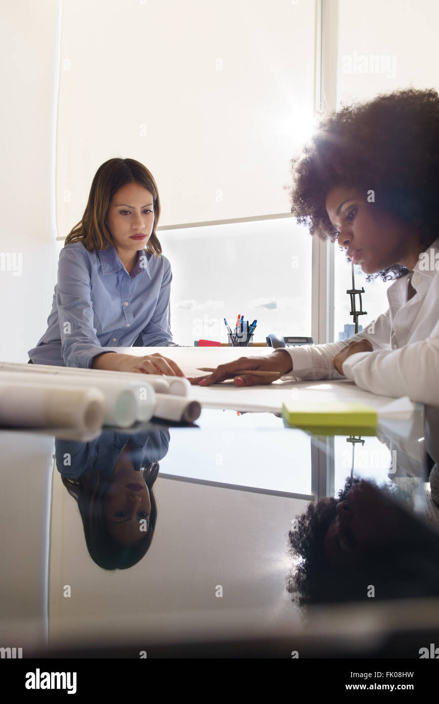 Team of two female architects, sitting at desk in office. The women talk reviewing a building plan. Reflections - Stock Image