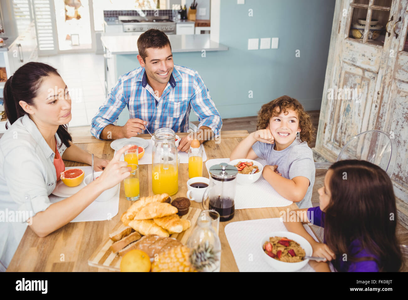 Happy family eating breakfast at table in house - Stock Image