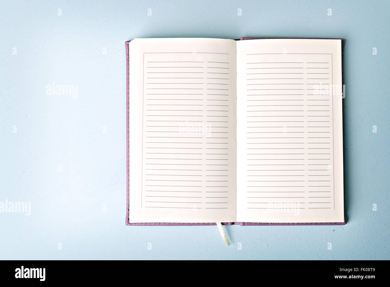 opened notebook on blue table, flat lay - Stock Image