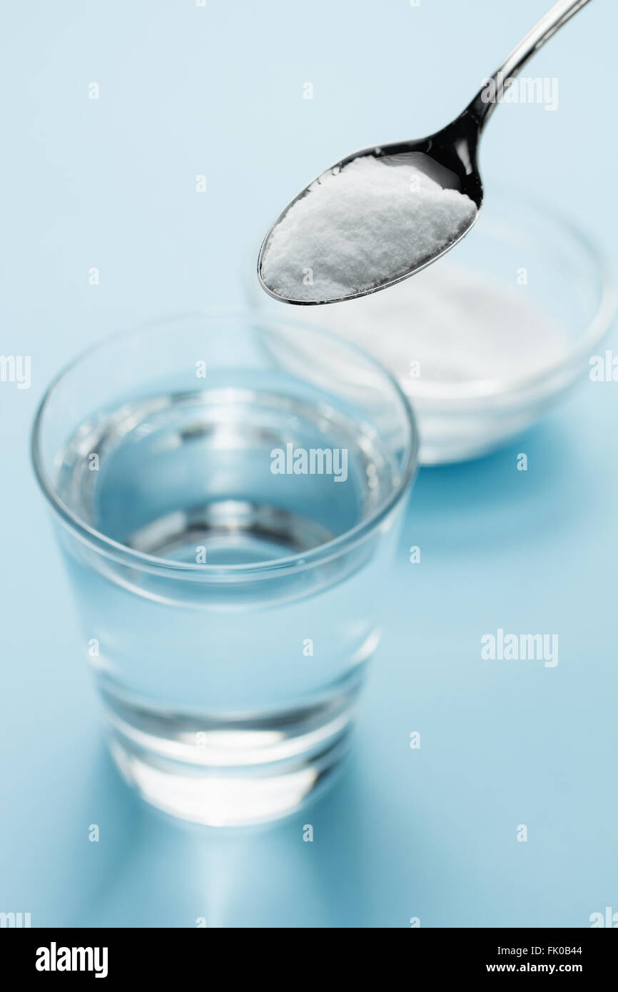 Spoon of baking soda above a glass of water on blue background - Stock Image