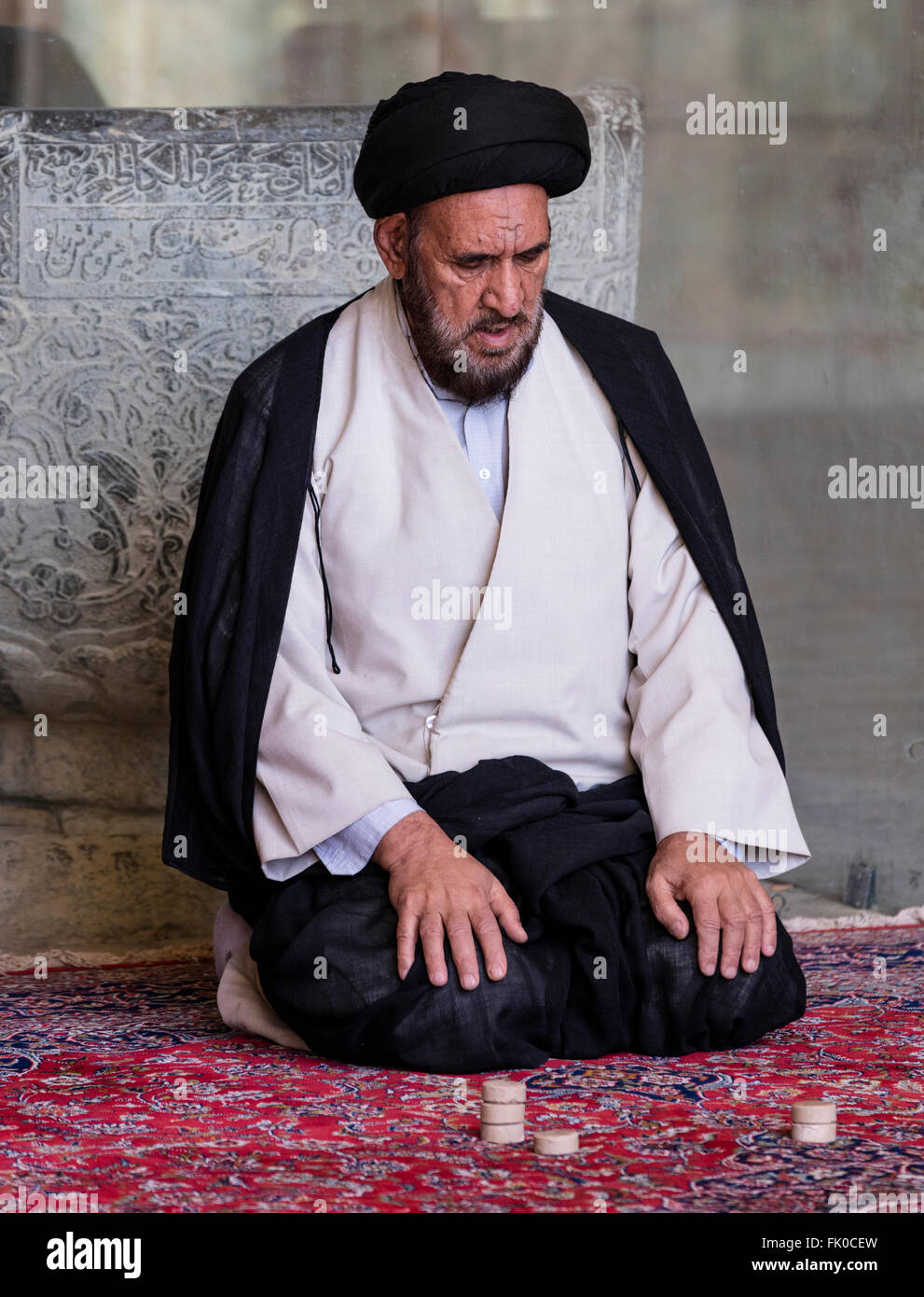Shia Muslim mullah in turban and gown seated at prayer in the Masjed-e Jame (Friday Mosque), Isfahan, Iran - Stock Image