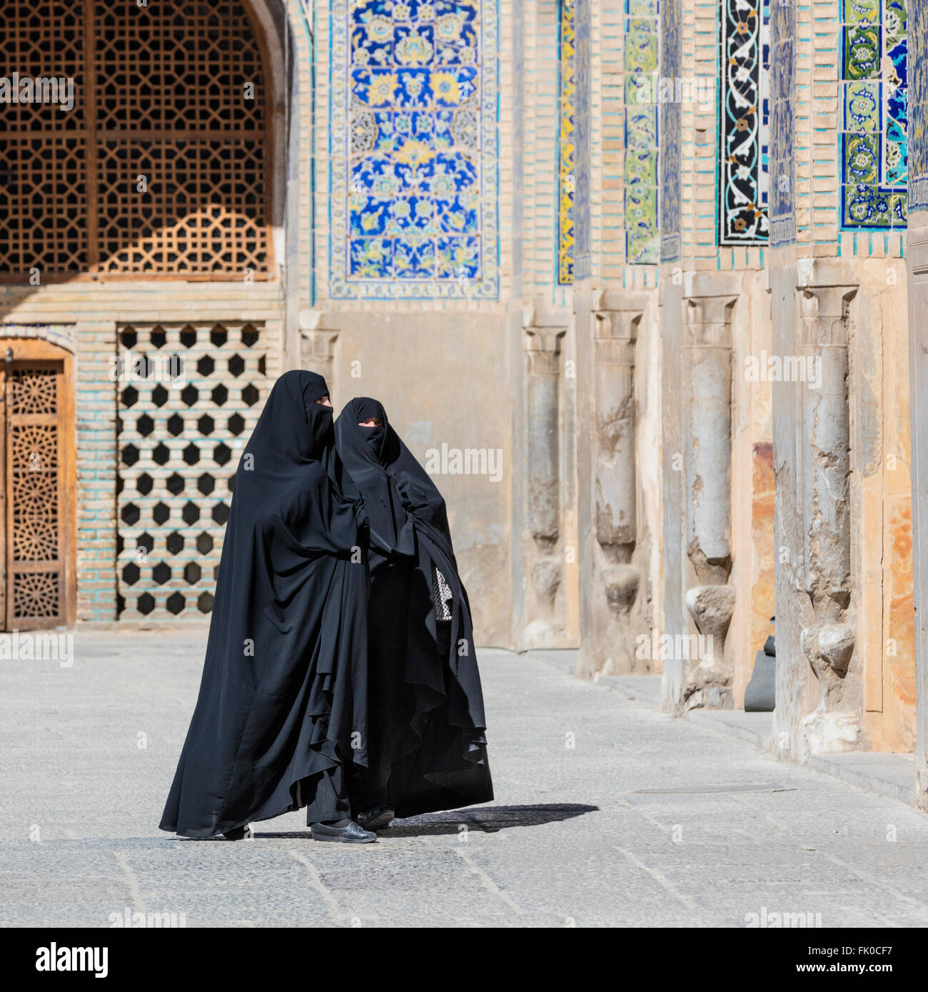 Two women in burkas stand in the courtyard of the Masjed-e Imam (Imam's Mosque) near the Maydan-e Imam Isfahan - Stock Image