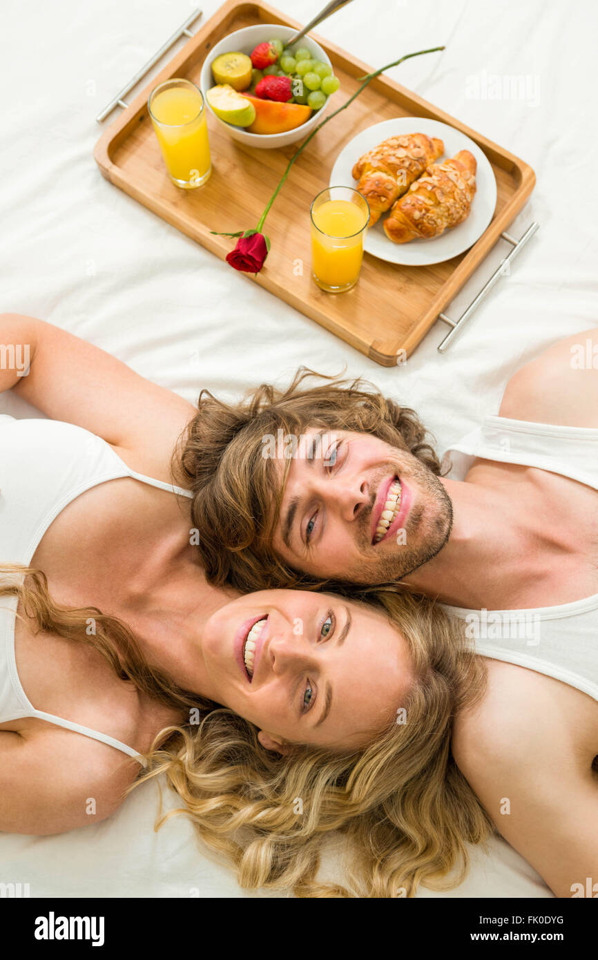 Cute couple lying in bed next to a breakfast tray - Stock Image