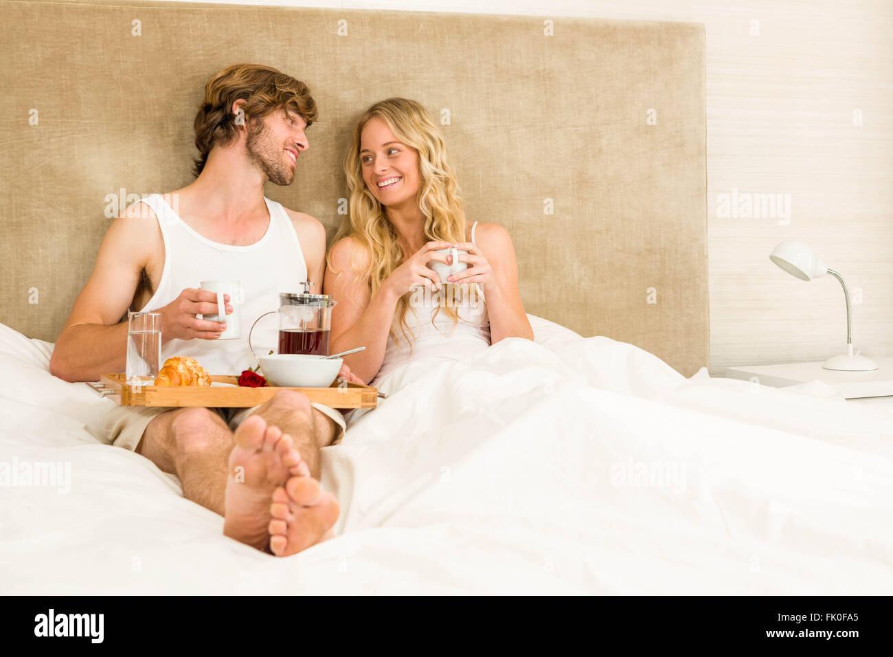 Cute couple having breakfast in bed Stock Photo
