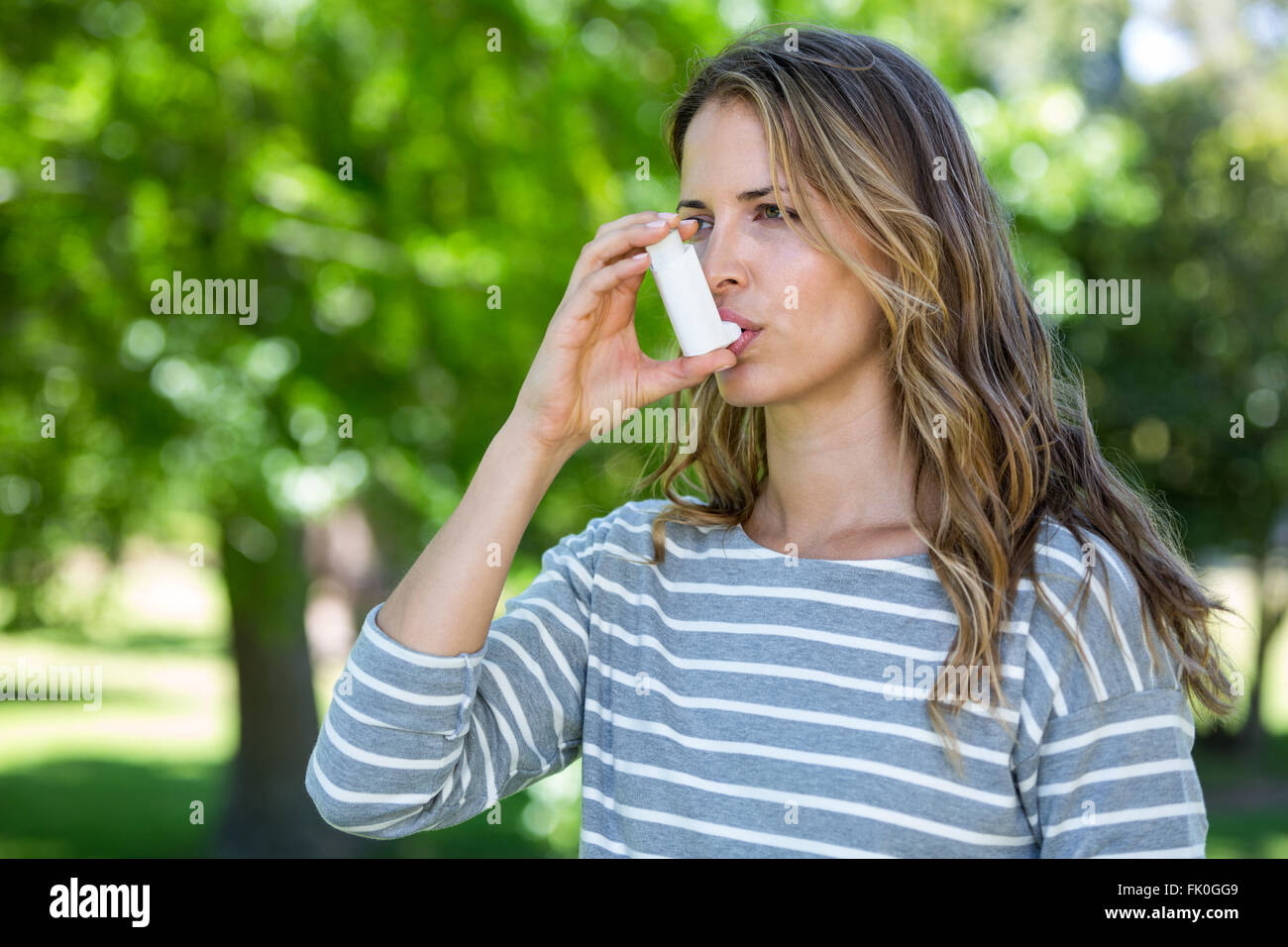 Woman using asthma inhaler - Stock Image