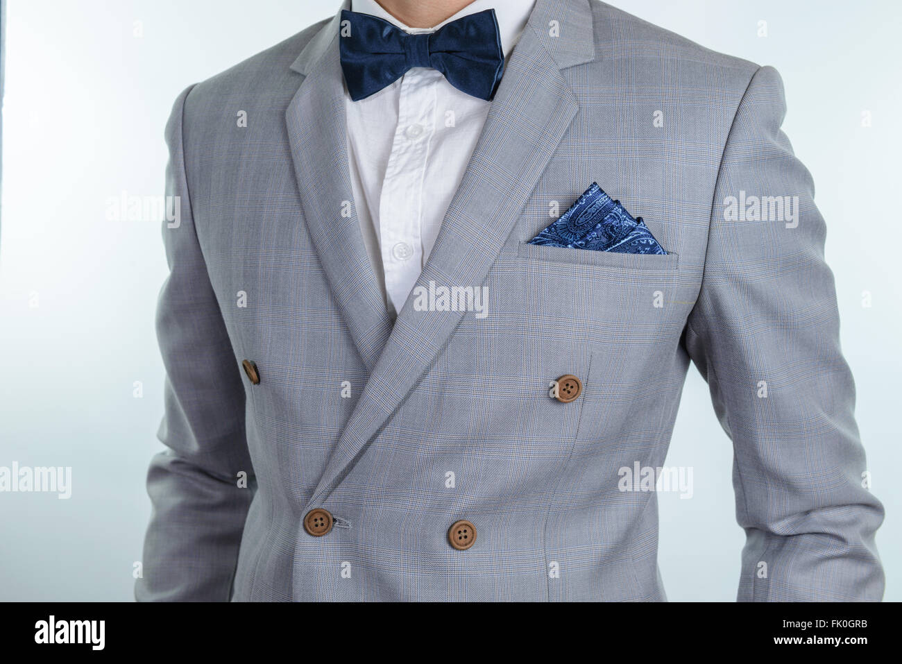 Man in grey suit, plaid texture, blue bowtie and pocket square, close up white background - Stock Image