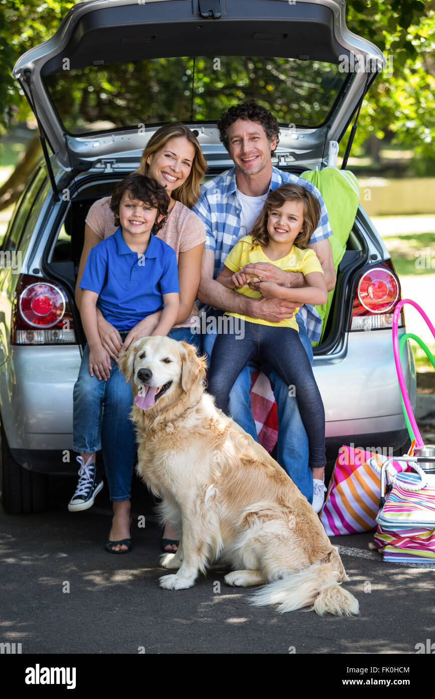 Smiling family sitting in the luggage space - Stock Image