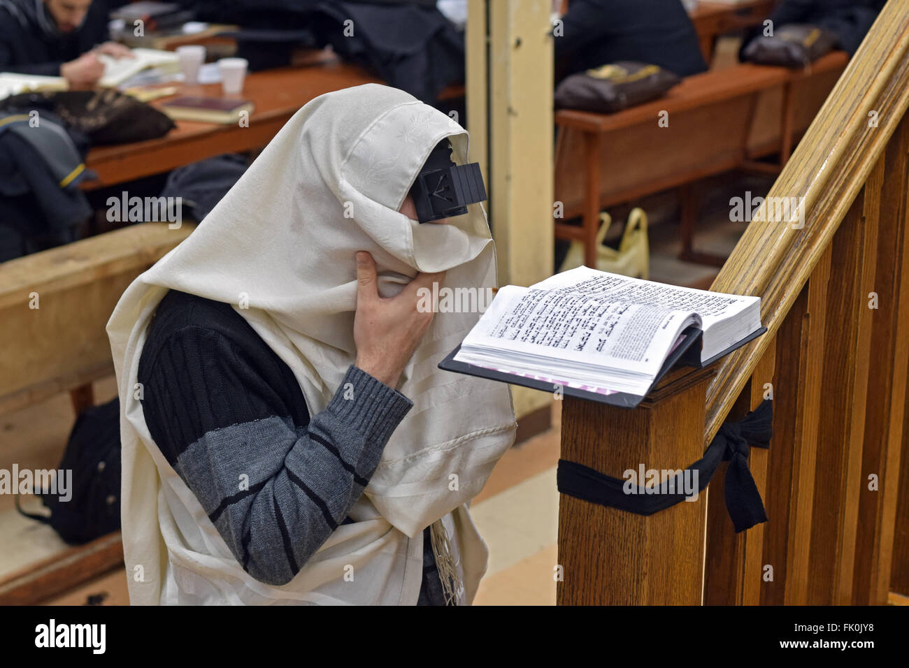 A young religious Jewish man hides his eyes with his Tallit while saying the Shema prayer at a synagogue in Brooklyn, - Stock Image