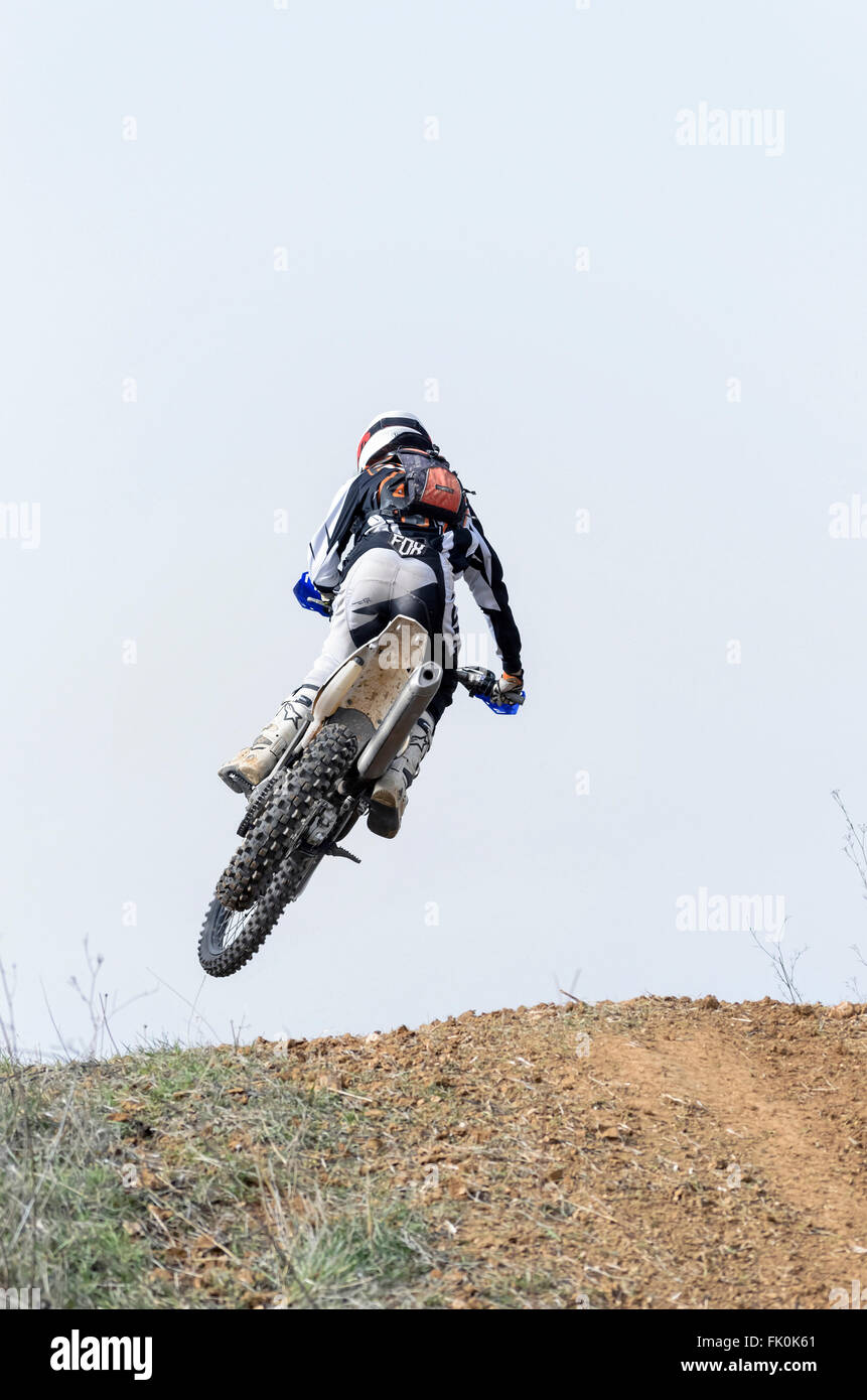 Spain cross country championship. Motorcyclist is jumping with his motocross motorcycle, during first race of season - Stock Image