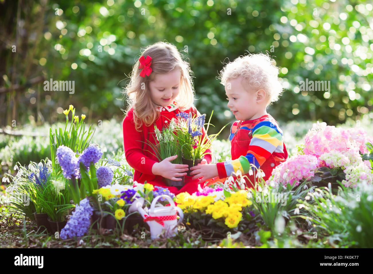 Children Planting Spring Flowers In Sunny Garden Little Boy And