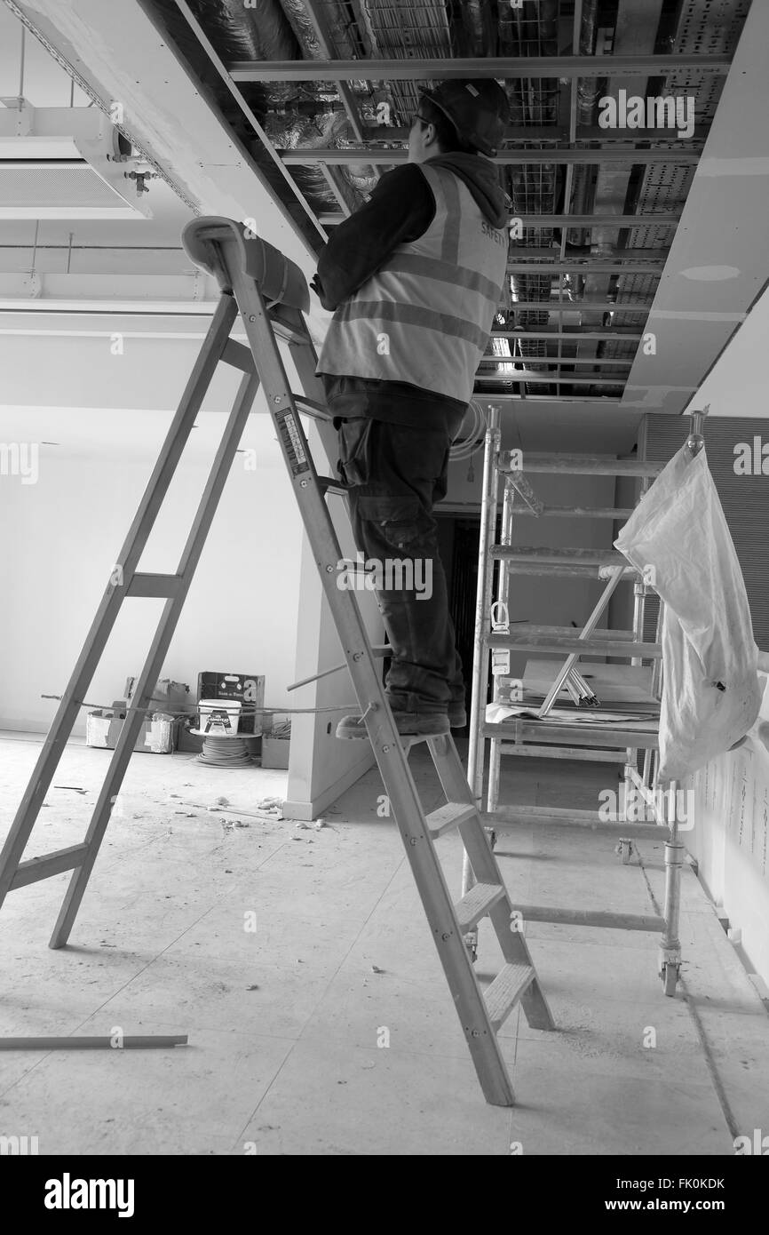 An electrician working o a set of steps into a ceiling void on a construction site. February 2016 - Stock Image