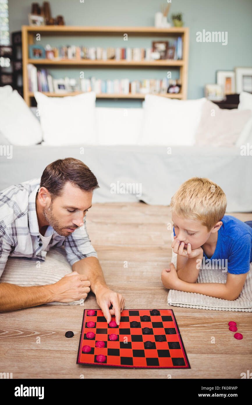 Father and son playing checker game at home Stock Photo