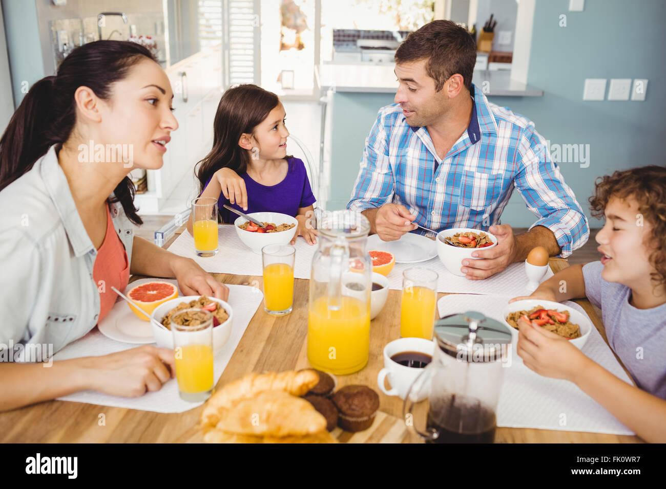 Happy family talking while having breakfast - Stock Image