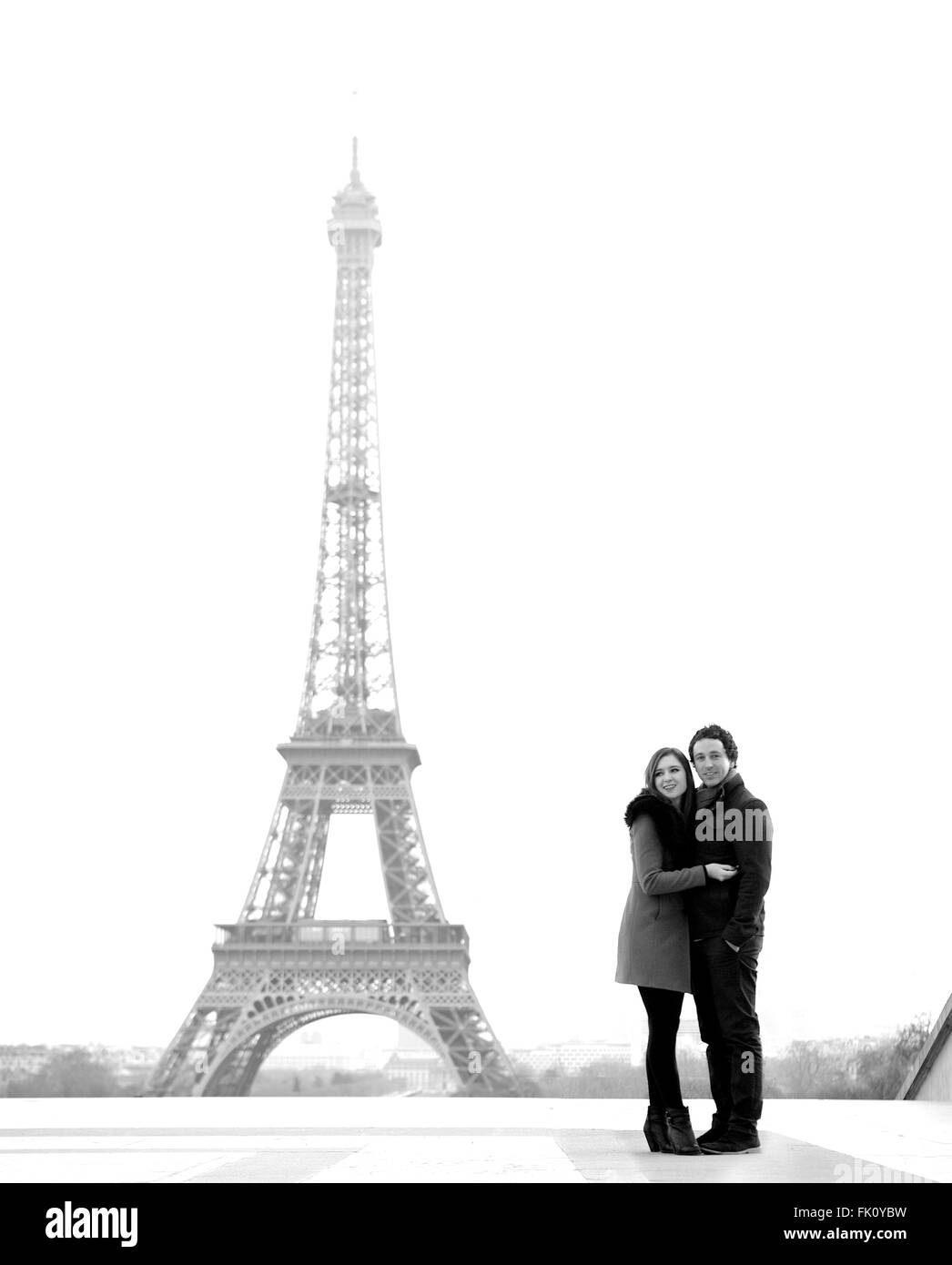 Young and in love brunette couple in front of Eiffel tower, Paris, at Trocadero overlooking the city during the Stock Photo