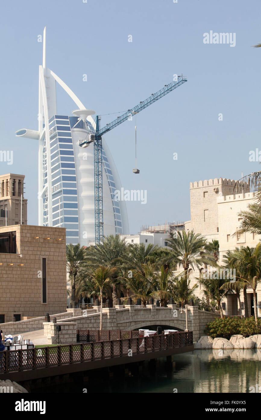 Dubai's symbol Burj Al Arab hotel photographed along with construction crane - Stock Image