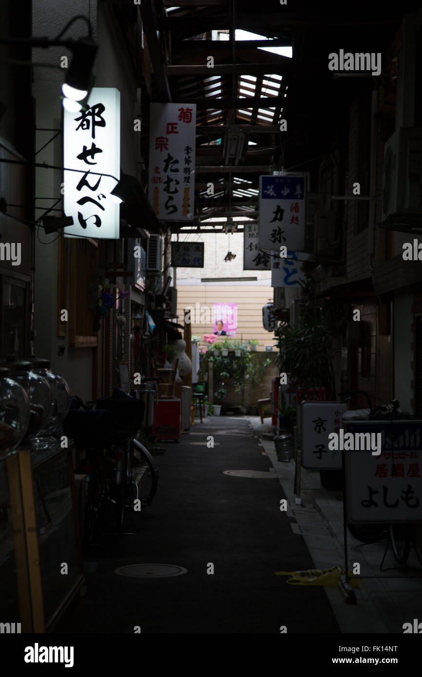 A small, darkly lit alley in the narrow streets of Yanaka Ginza in Tokyo, Japan. - Stock Image